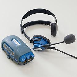 ▲同社が導入している「ボイスシステム」のマイク、スピーカー一体のヘッドセット(インカム)と端末機